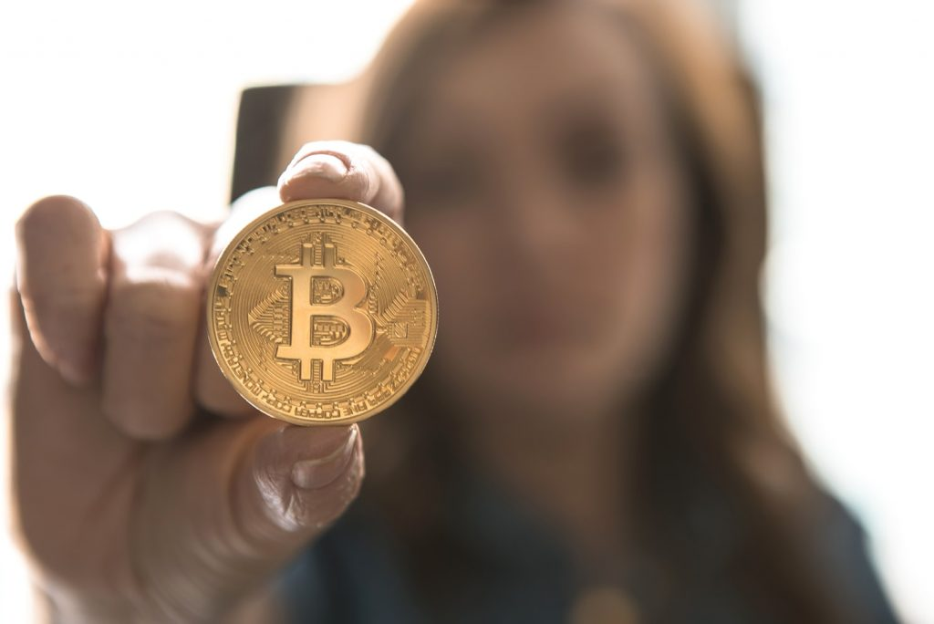 woman entrepreneur holding bitcoin for this market cycle blog written by money mindset coach Lowina